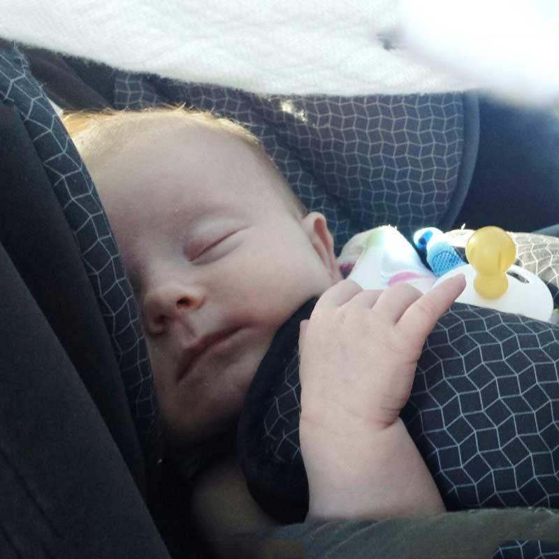Kleines Baby schläft im Autositz