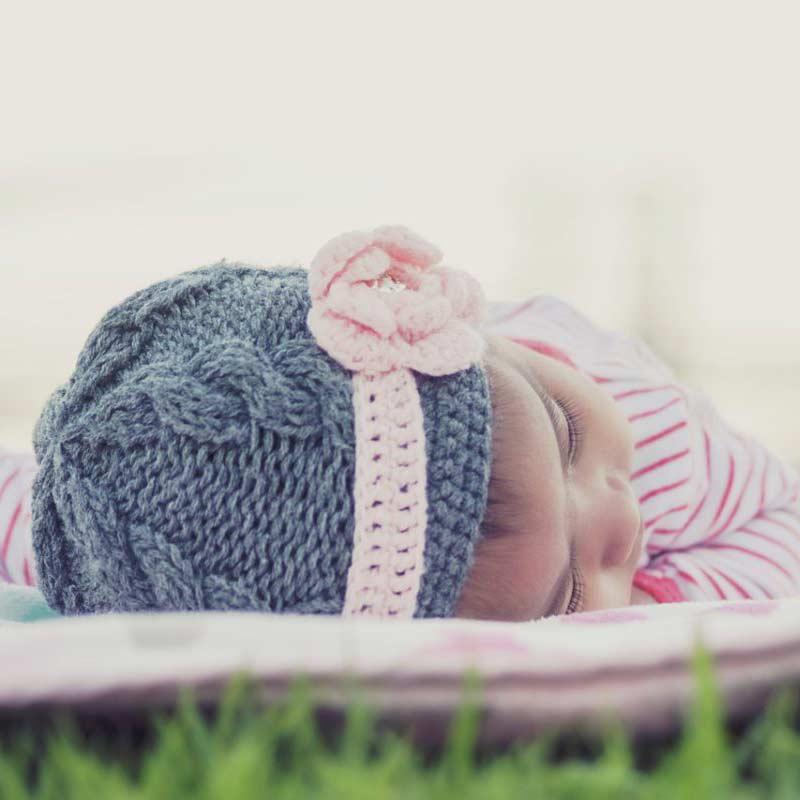 Mädchen mit Wollmütze schläft auf Rasen