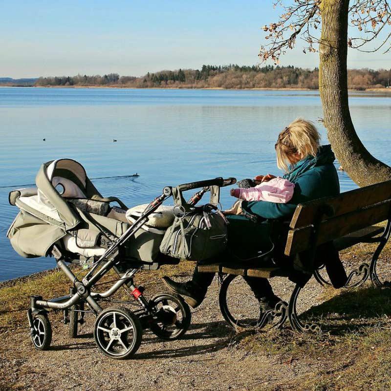 Frau am See mit Kinderwagen