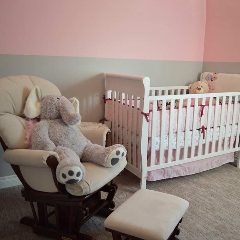 Kinderzimmer mit Babybett und Stillsessel