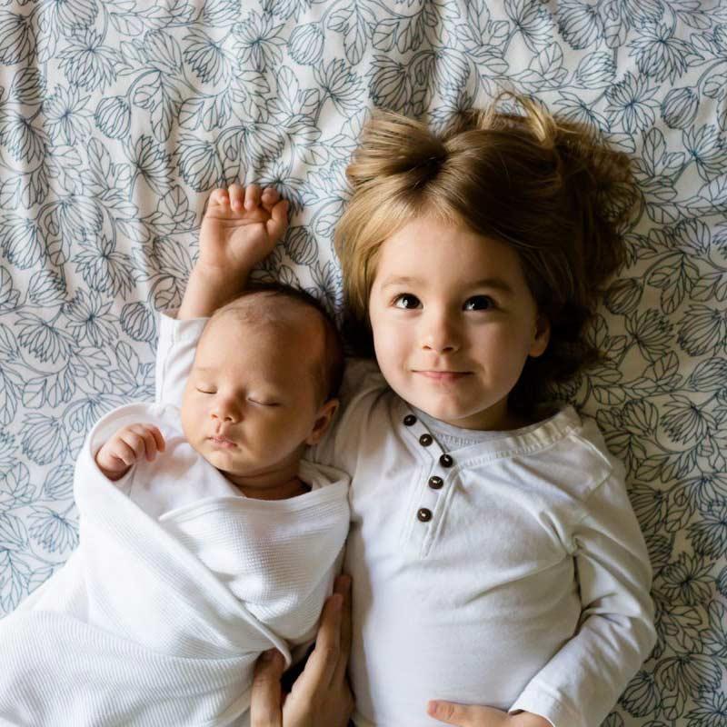 Zwei Kinder liegen friedlich auf einem Bett