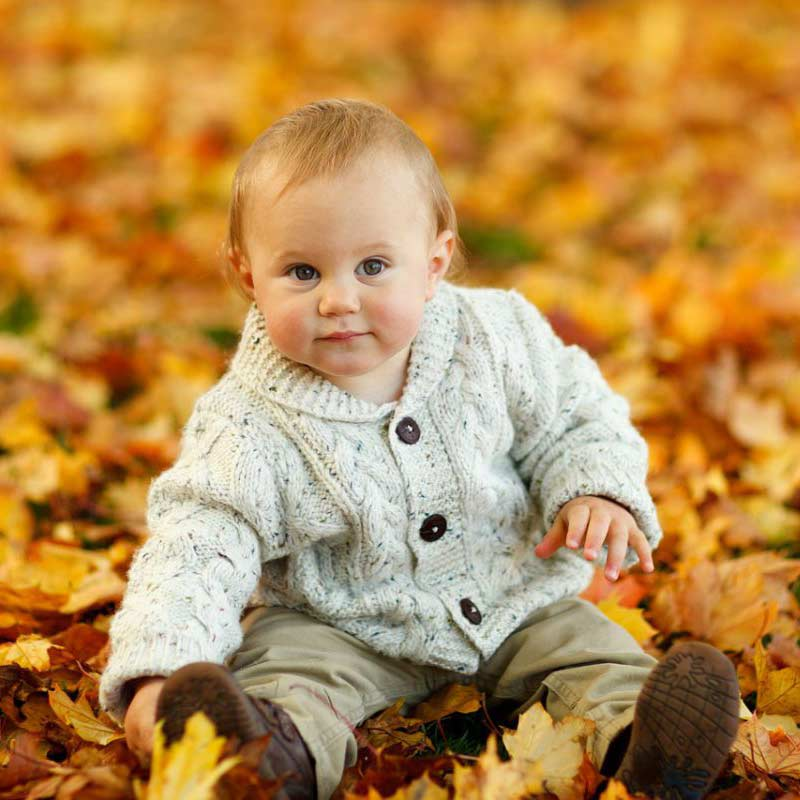 Kleiner Junge mit Jacke im Herbstlaub