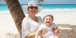 Mutter und Baby entspannten bei Sonnenschein am Strand